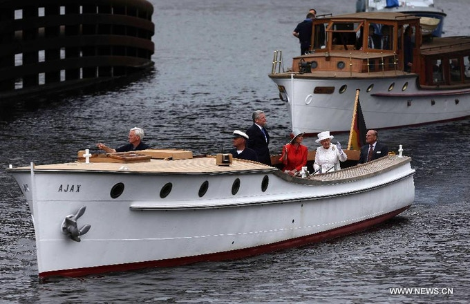 Queen Elizabeth and Prince Philip are followed by their entourage on a barge, which Seiple helped restore.