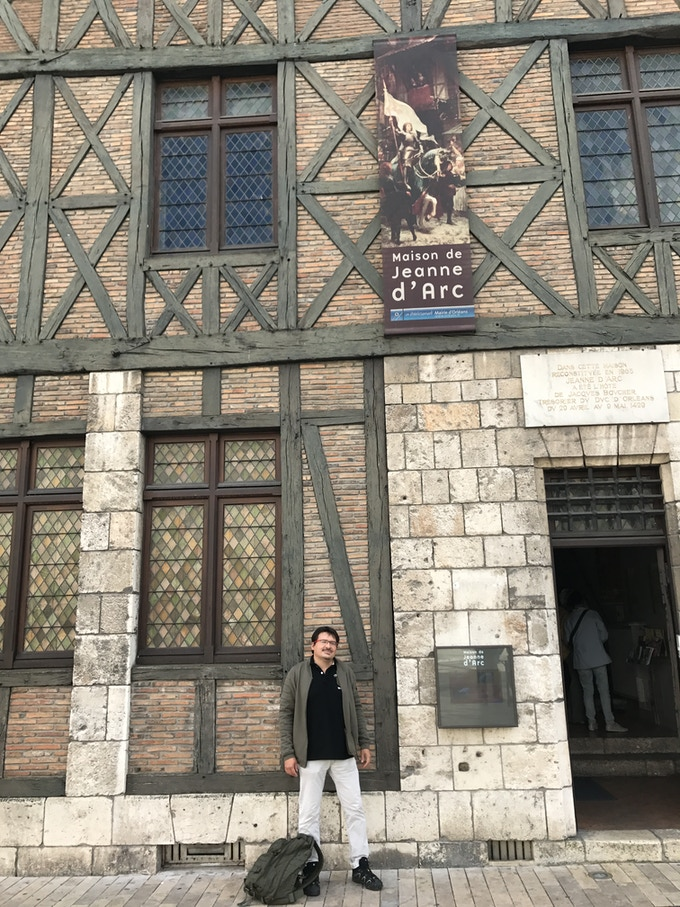 "Pascal Bernard, author of the game, in front of the ""Joan of Arc house"" in Orléans, the house in which Joan spent the night during the Siege of Orléans."