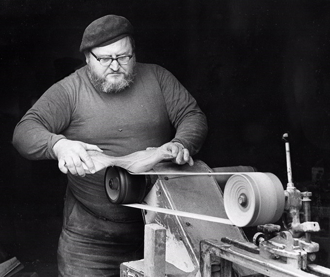 "Emil Milan using the ""Emil Machine,"" a combination slack belt and drum sander that he designed and built himself. Photo: William Wellman"