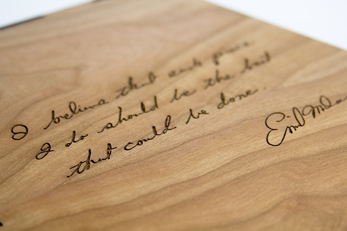 """Back of wood slip case with laser etched Milan quote. """"I believe that each piece I do should be the best that could be done."""" —Emil Milan"""
