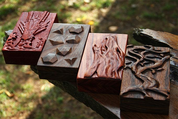 From left to right: Padauk with Fire Dragon Sculpted Design, Black Walnut with Polys Sculpted Design, Bubinga with Howling Wolf Sculpted Design, Benge with Yggdrasil Sculpted Design.
