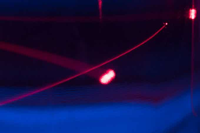 Lasers at different focus levels shining through a viscous fluid.
