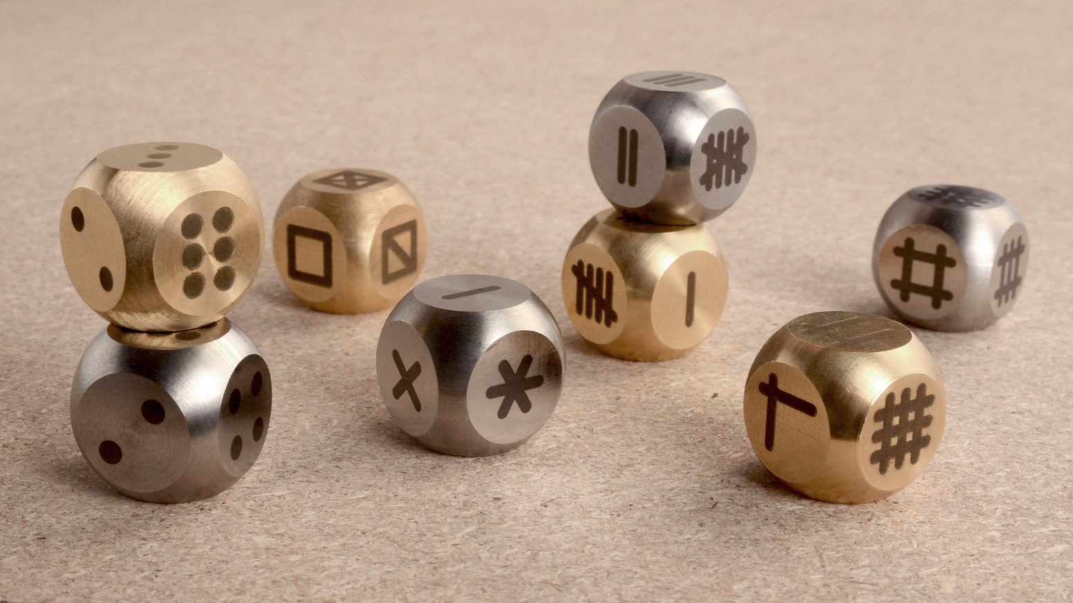 Upgrade your dice: a family of graphic alternatives to classic dots in Stainless & Brass.