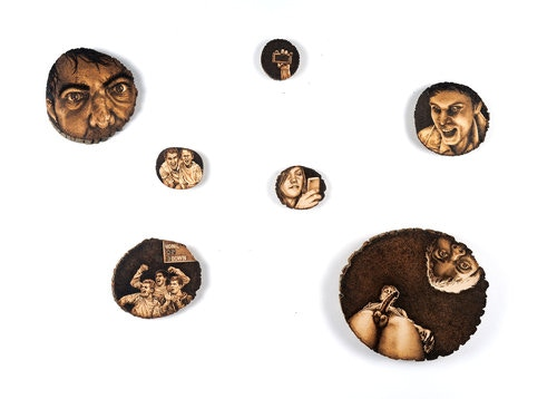 "One For The Team"", 2016, pyrography (wood burning) on tree slices, dimensions variable (2"" rounds to 12"" rounds)."