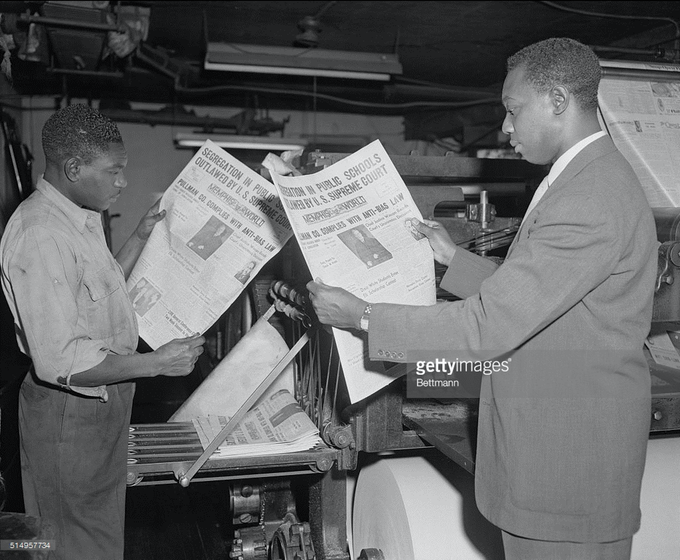 William Gordon (r), and pressman Kimber Boddie check a copy of the Memphis World. Getty Images.