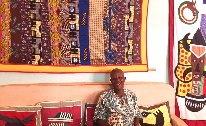Ives Appolinaire Pede in front of one of his unique tapestries