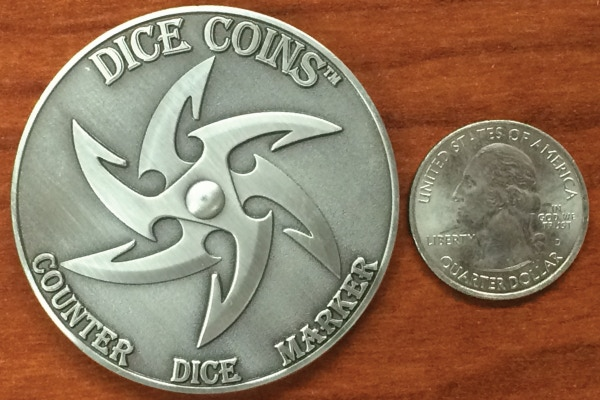Common side of a Dice Coin.  The spinning knob is in the center of the coin.  Coins are 2 inches in diameter.  They are much larger and thicker than a US quarter.