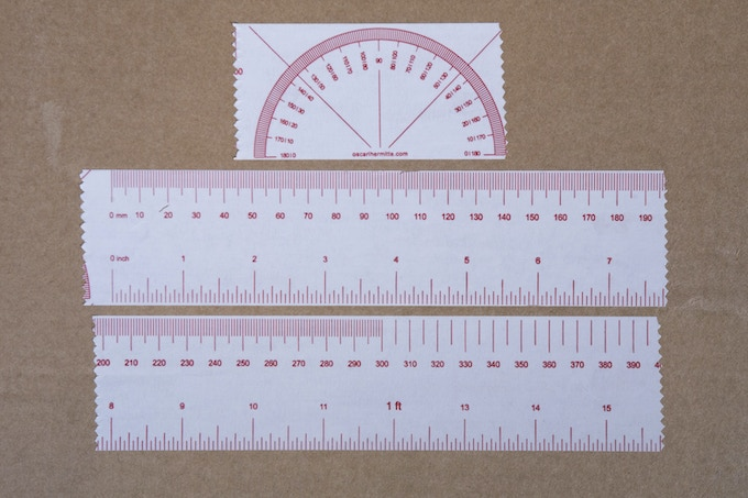 Metric and imperial ruler + protractor. Pattern repeated every 500mm (132 repetitions in total).  Red print on white, 48mm wide, high quality vinyl tape, 35micron, 66m long.