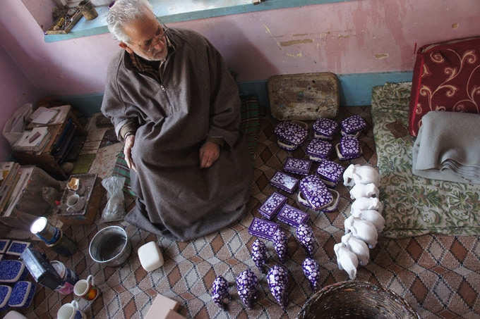 One of the artisans working in his home
