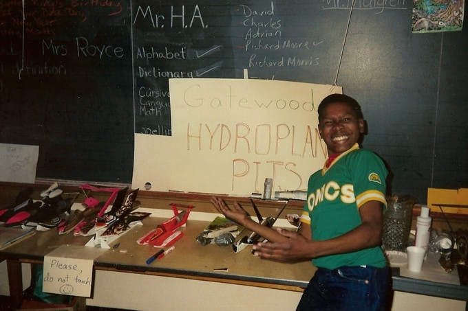 "Charles, a 5th-grader in 1985, shows off the different hydroplane designs in the ""pits."""