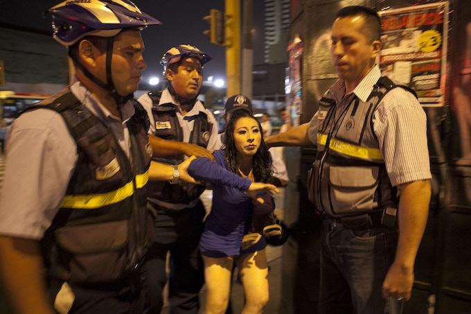 """Kiara é tomada por """"serenazgos"""", ou policiais municipais, nas ruas do centro de Lima, onde ela trabalha.  As mulheres trans são frequentemente presas e abusadas verbal e fisicamente pelos oficiais."""