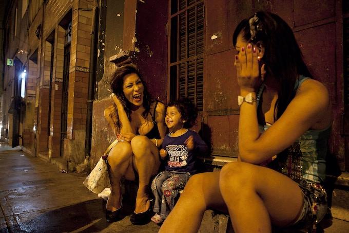 Danuska, à esquerda, e Oriana, à direita, conversam com uma jovem e sua mãe, não fotografadas, na rua, enquanto vivenciam o tempo de folga durante o trabalho.