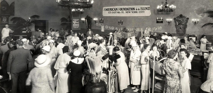 Blind Artisans Charity Market in Miami, Florida, circa 1929, in support of the American Foundation for Blind. Dozens of women and a few men mingle around various tables of goods for sale.