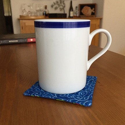 A coaster in action! Yours will have book art on one side.