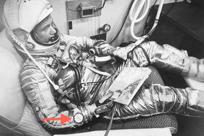 Astronaut John Glenn with stopwatch on wrist inside Friendship 7 capsule prior to Mission Atlas 6 launch.