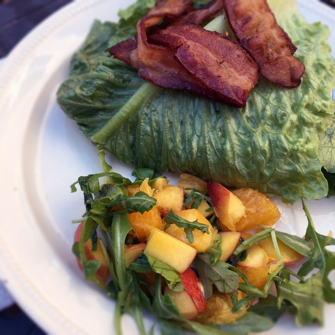 Lettuce-wrapped burger with a fresh mango salad.