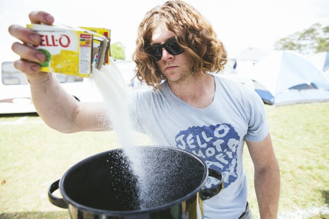 Paul making jello shots at a music festival in the wild.