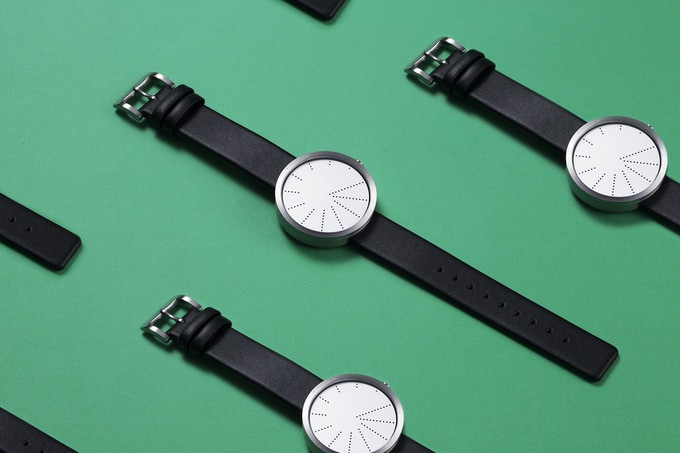 The simple design is made of a perforated watchface with a dot for each hour.