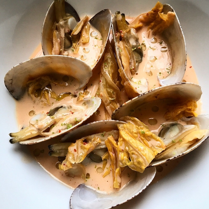Clams cooked in a coconut and kimchi cream with lime rind and chive oil