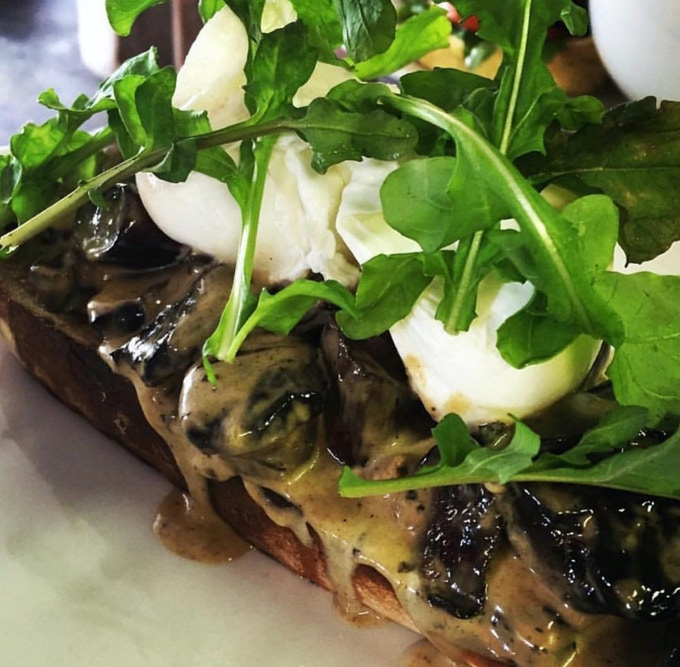 Mushrooms on grilled sourdough with two poached eggs and rocket