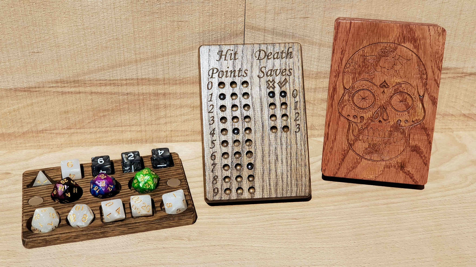 A dice box with integrated hit point tracker & death saves tracker, carved from solid Oak and using neodymium magnets and steel balls.