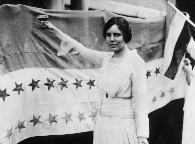 Alice Paul holding glass in front of the ratification banner.  August 26, 1920.