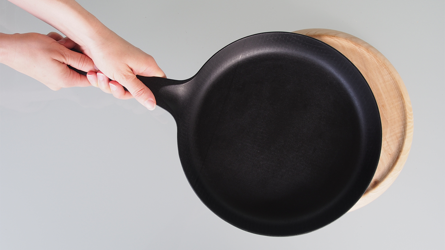 Cast iron cookware for performance and presentation – a longer handle, smooth surface, lightweight design, and hardwood accessories.