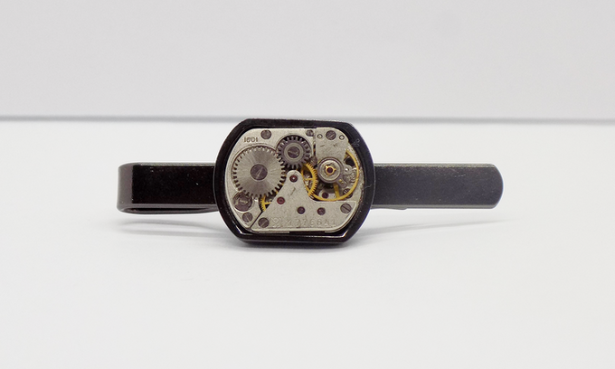 Tie bar in black with small rectangular watch movement with an epoxy protective layer