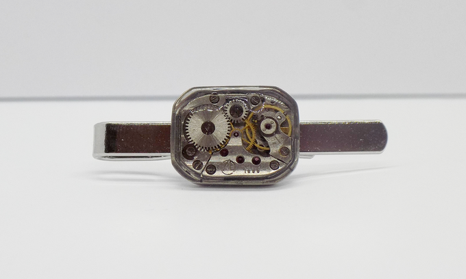 Tie bar in silver with large rectangular watch movement with an epoxy protective layer