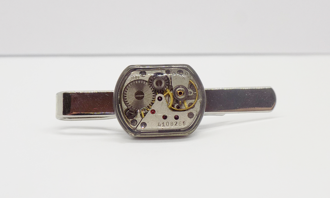 Tie bar in silver with small rectangular watch movement with an epoxy protective layer