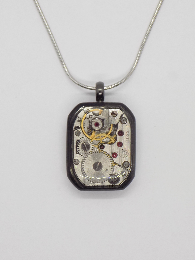 Watch movement pendant in black with a large rectangular movement in with a protective epoxy coating