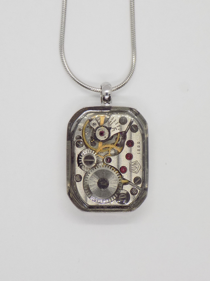 Watch movement pendant in silver with a large rectangular movement in with a protective epoxy coating