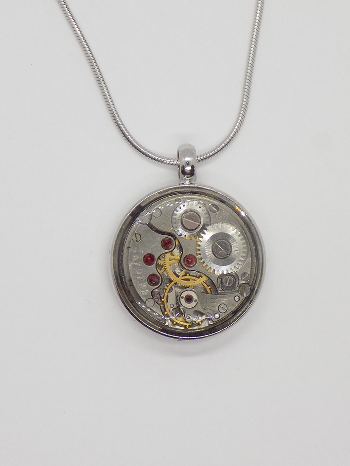 Watch movement pendant in silver with a round movement in with a protective epoxy coating