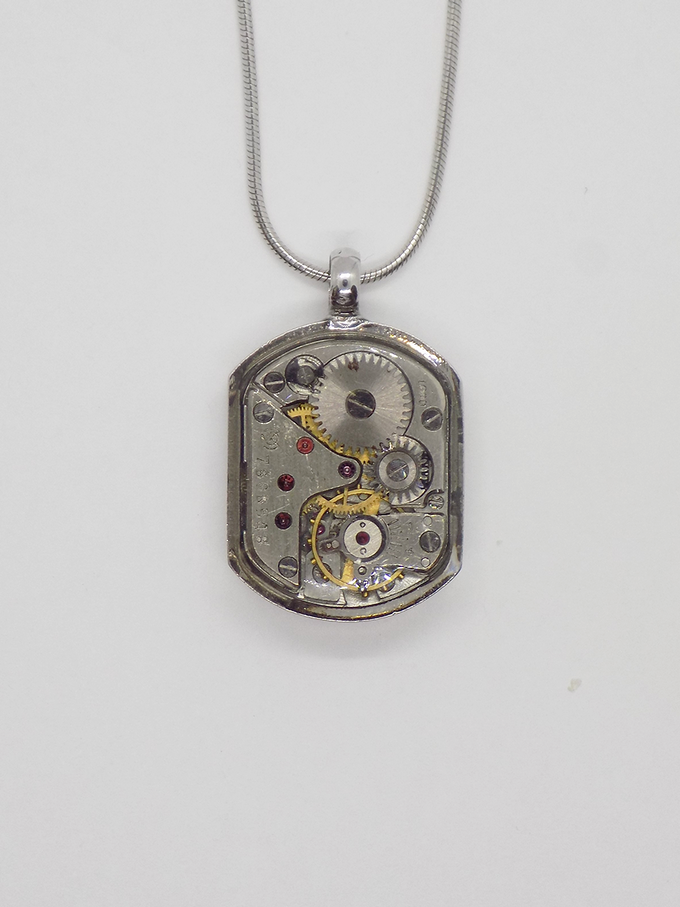 Watch movement pendant in silver with a small rectangular movement in with a protective epoxy coating