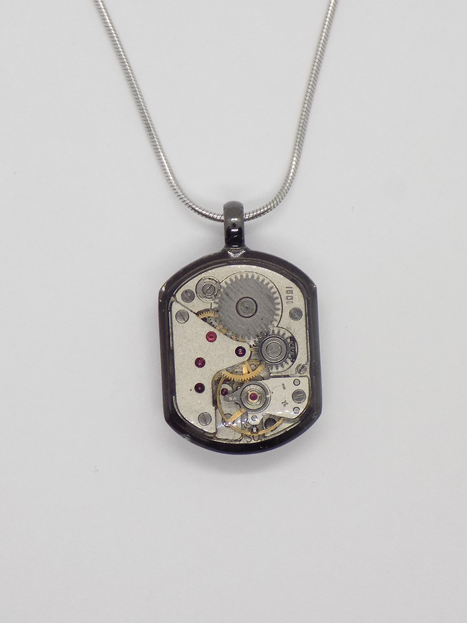 Watch movement pendant in black with a small rectangular movement in with a protective epoxy coating
