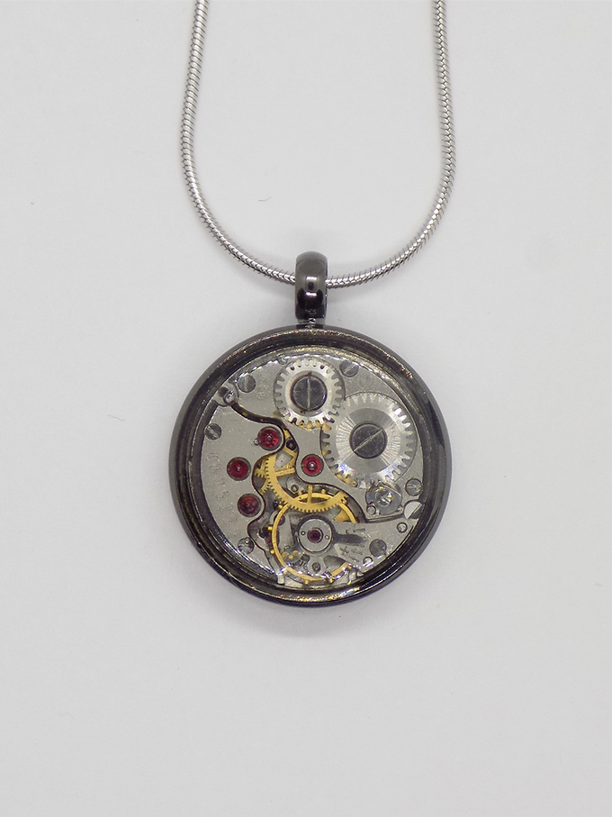 Watch movement pendant in black with a round movement in with a protective epoxy coating