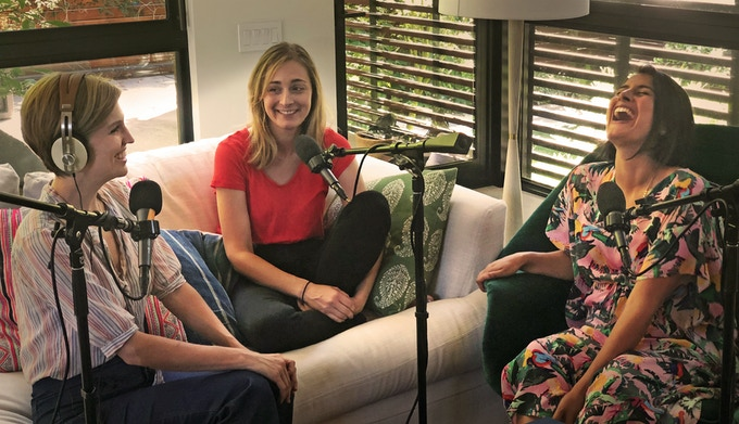 Women laughing while podcasting.