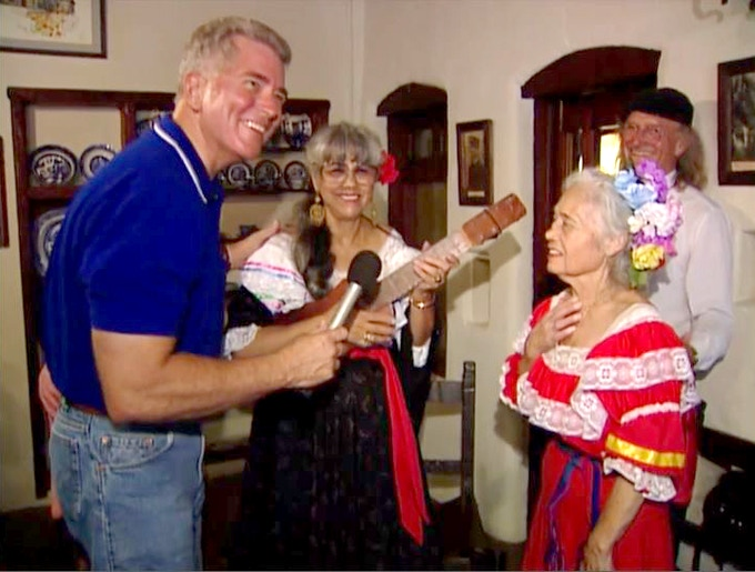 """Huell Howser takes in a performance of the song, """"La Noche Está Serena,"""" at the Lummis House in Highland Park."""