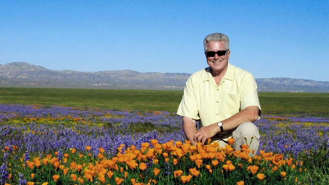Huell Howser in a field of California Poppies.