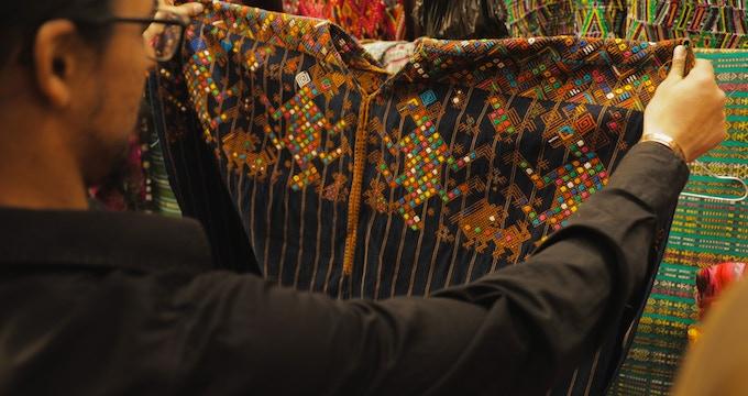 Valentino Romero holding up a Huipil (Mayan blouse).