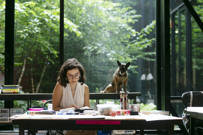 Creator-in-Residence Maëlle Doliveux working on her book project, with her dog Leeloo looking on.