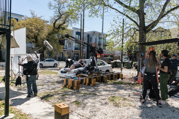 BTS photo of cast and crew mid-take, during a flashback scene in Savannah, GA