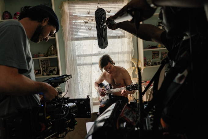 Cinematographer Lance Kuhns captures actor Peter Vack playing guitar in a Childhood Bedroom flashback scene, as Tres Savid mixes sound