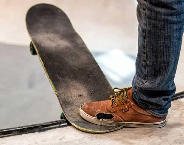 Broken skateboarding shoe due to sandpaper grip.