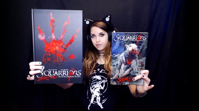 Squarriors artist Ashley Witter holding up the Squarriors Volume 1: Spring trade paperback next to the oversize hardcover edition of Squarriors Volume 1!