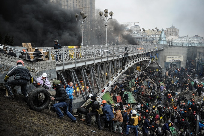 Euromaidan protesters pass tires to each other that were used to create a smoke screen during the shooting on February 20, 2014. Photo by Alexey Furman.