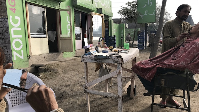 Curbside barbers ply their trade along the Grand Trunk Road of Pakistan.
