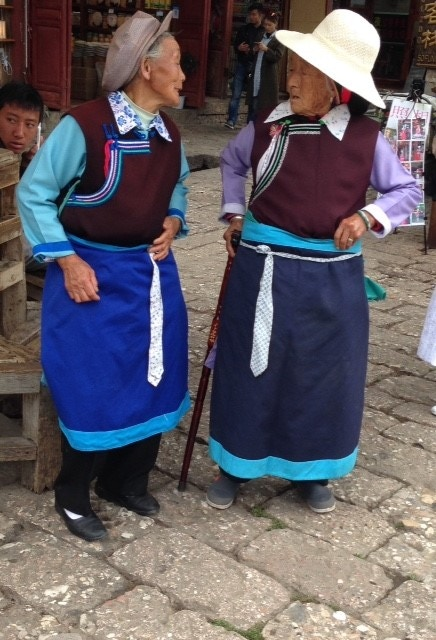 Two vibrant Naxi ladies in Lijiang, Yunnan Province  photo: Burnett Thompson