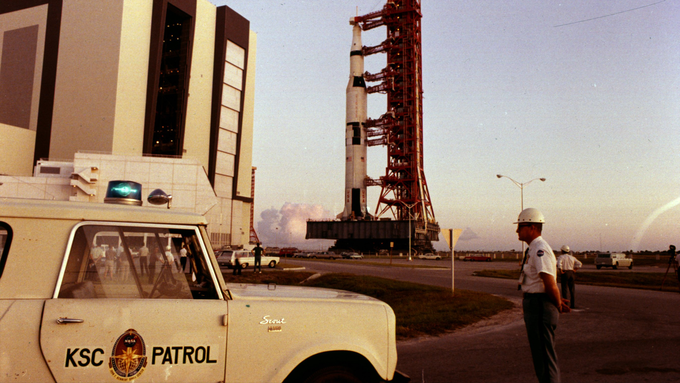 A NASA worker stands guard as the Saturn V rocket rolls out to the launch pad.