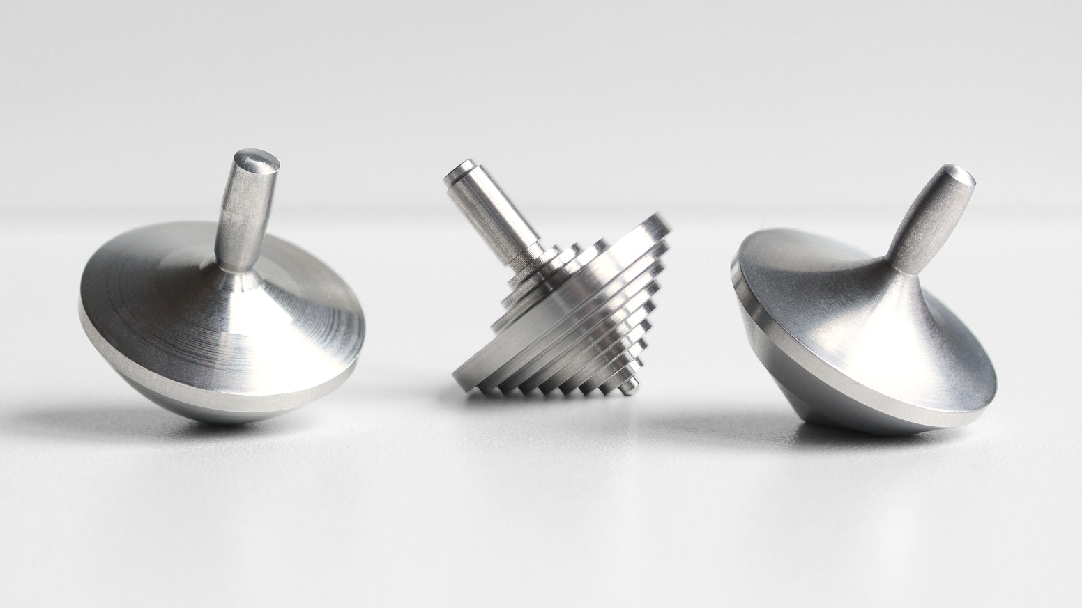 Three artful stainless steel spinning tops, wrapped in a hand-crafted leather case.